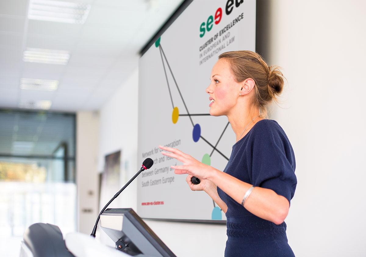see eu Cluster of Excellence in European and International Law Europainstitut Saarland Corporate Design Frau haelt Praesentation ins Mikrofon sprechend PowerPoint Titelchart auf Leinwand im Hintergrund