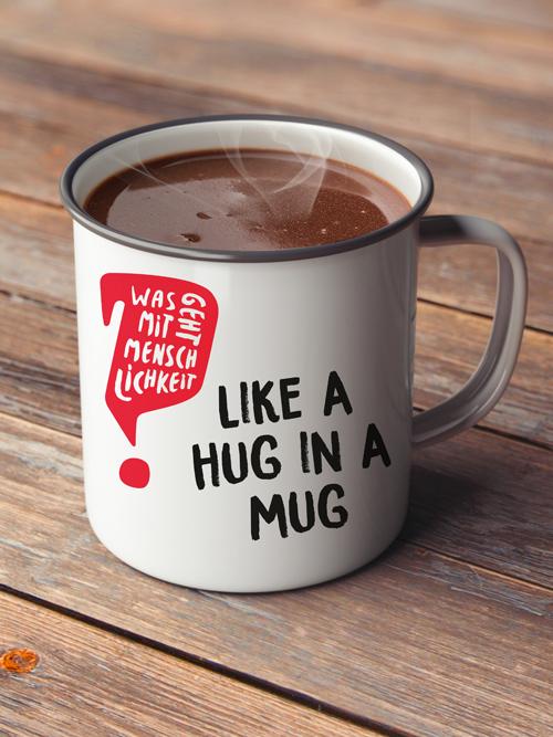 Jugendrotkreuz Was geht mit Menschlichkeit? Kampagne Trinkbecher aus Emaille gefüllt mit Kakao Aufschrift like a hug in a mug mit Logo Holztisch