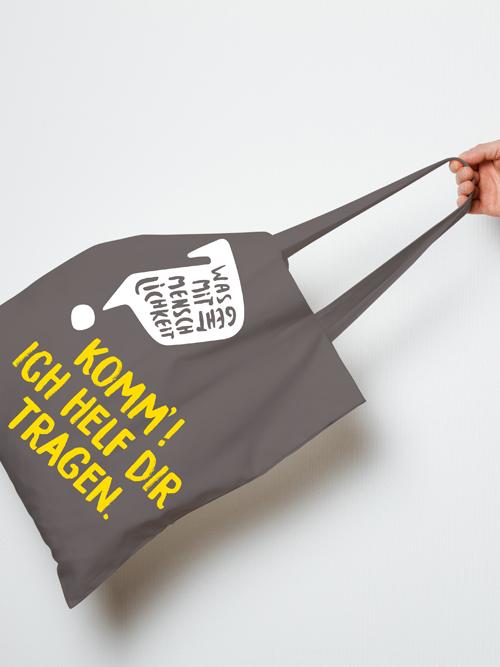 Jugendrotkreuz Was geht mit Menschlichkeit? Kampagne grauer Jutebeutel mit Logo und Spruch Komm! Ich helf dir tragen.