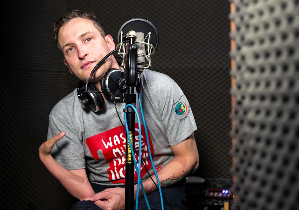Jugendrotkreuz Was geht mit Menschlichkeit? Kampagne Testimonial Graffidi mit Kampagnen-T-Shirt im Tonstudio hinter Mikrofon sitzend