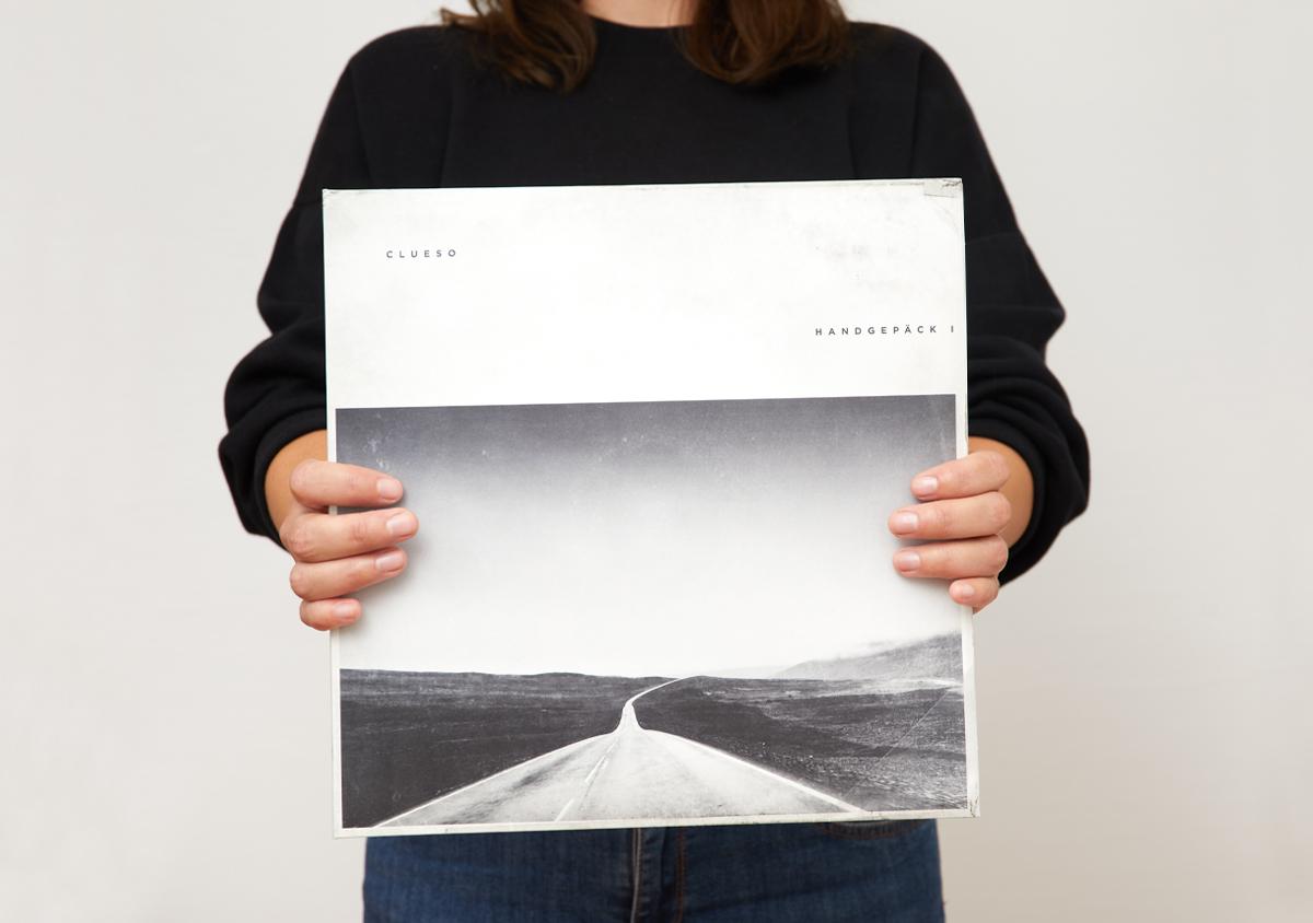 Frau haelt Clueso Handgepaeck 1 Album Plattencover