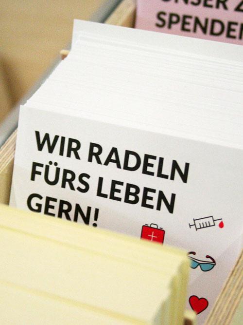 jungesblut spenden dkms gesamtschule kamen corporatedesign gelber weisser und rosa Postkarten Stapel mit Icons in Holzkiste