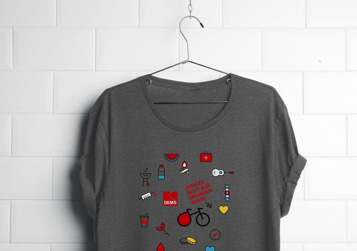 jungesblut spenden dkms gesamtschule kamen corporatedesign graues T-shirt mit Icons und logo hängt an Drahtbügel vor weisser backsteinmauer