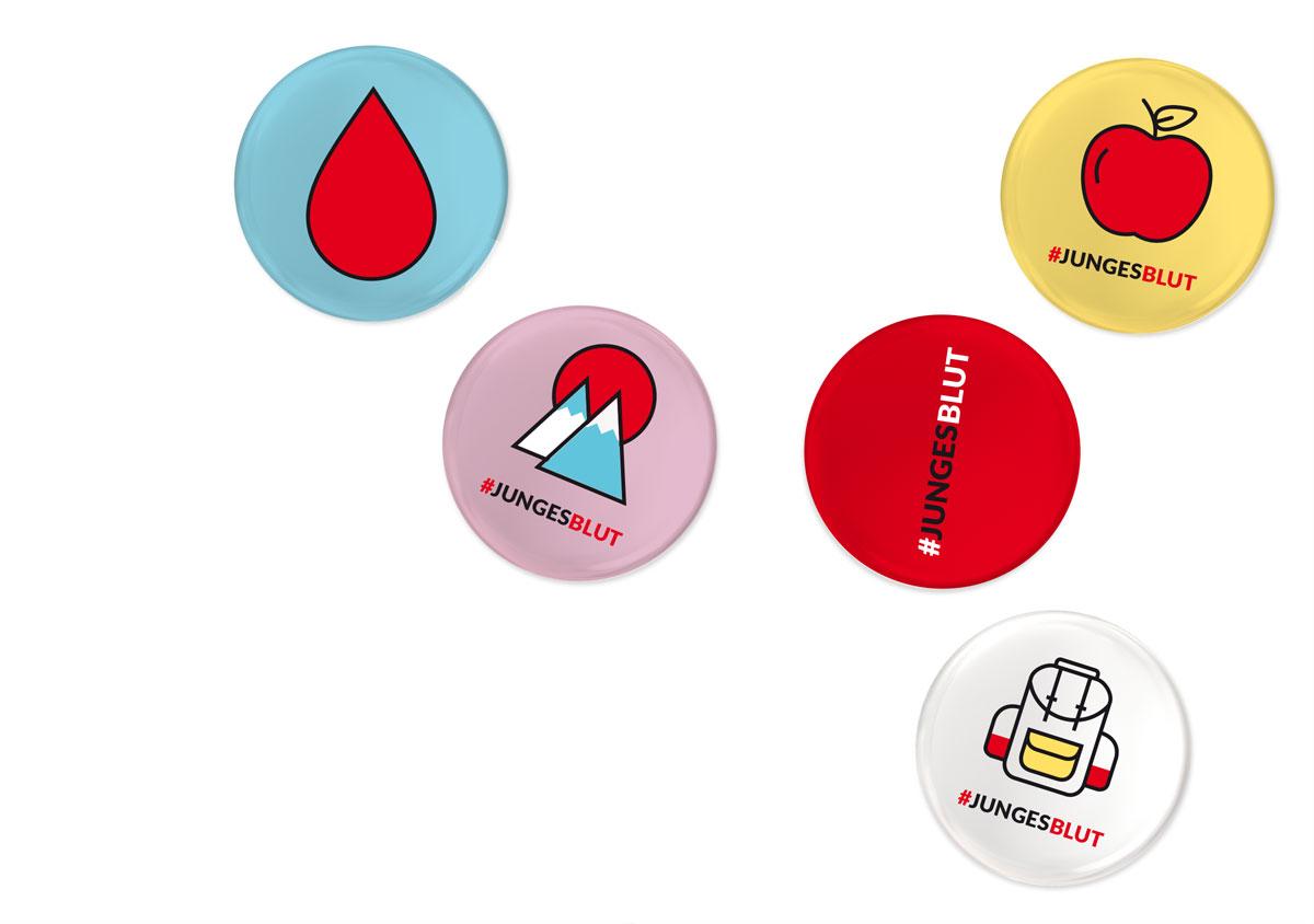jungesblut spenden dkms gesamtschule kamen corporatedesign Buttons fuenf Anstecker auf Tisch in den farben hellblau rosa rot gelb weiss aufgedruckte icons Blutstropfen Berge Apfel Rucksack #jungesblut
