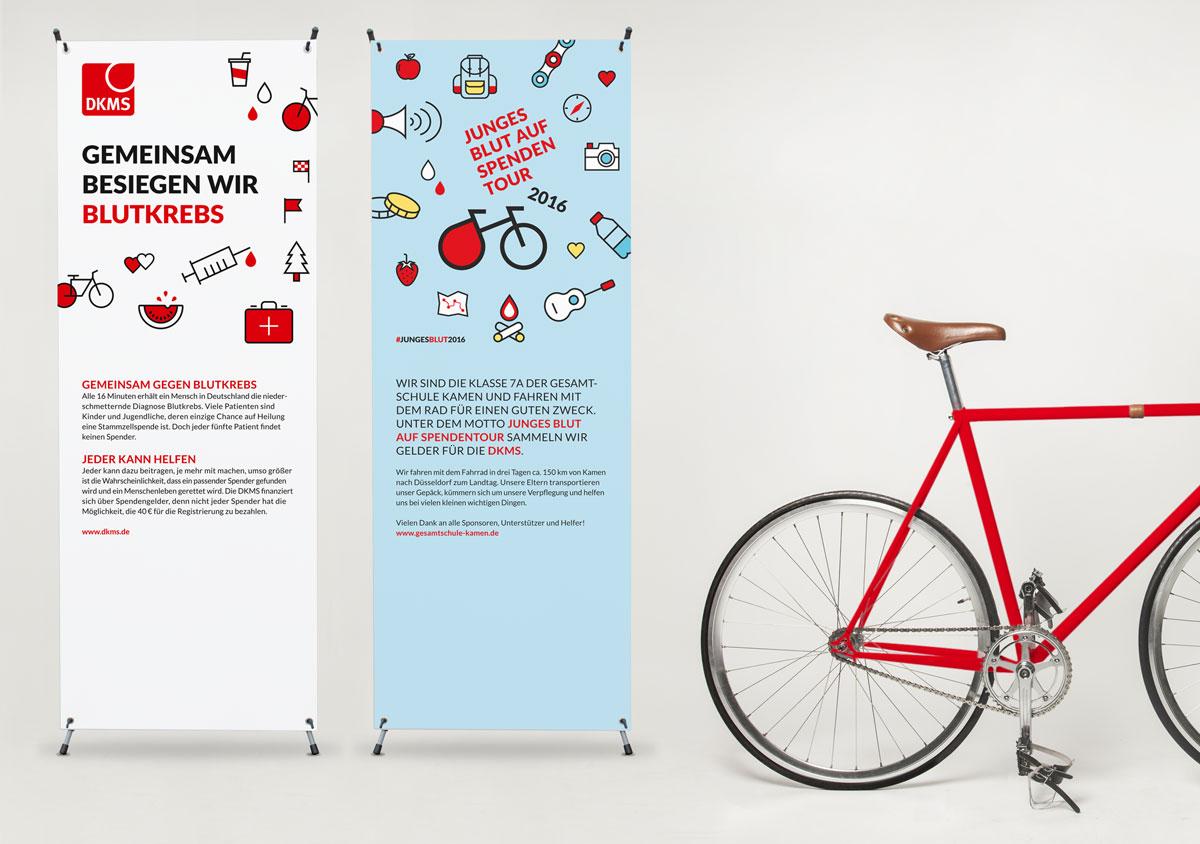 jungesblut spenden dkms gesamtschule kamen corporatedesign zwei Rollups stehen neben einem roten Fahrrad im raum aufstellen mit Informationen Logos Icons und Spendenaufruf