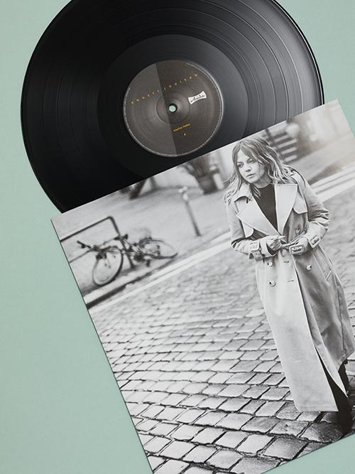 vinyl schwarz-weiss Innersleeve und LP Side A auf mintgruenem Untergrund Porträt im Trenchcoat im Hamburger regen Kopfsteinpflaster