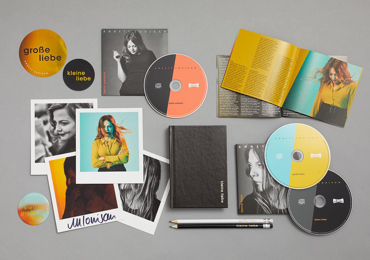 packshot vom fanbox-inhalt auf grauem Untergrund Aufkleber Bonus-CD CD-booklet Postkarten Autogrammkarte Notizbuch Stifte Digipack mit zwei CDs Kuehlschrankmagnet