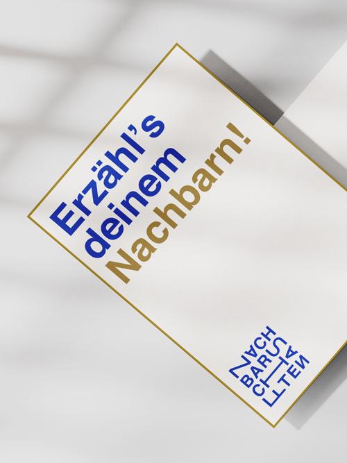 Flyer Karte weiß liegend auf hellgrauem Tisch Lichtreflexe auf dem Untergrund Blauer und goldener Text links oben auf der Karte goldene Umrandung Nachbarschaften-Logo in blau links unten