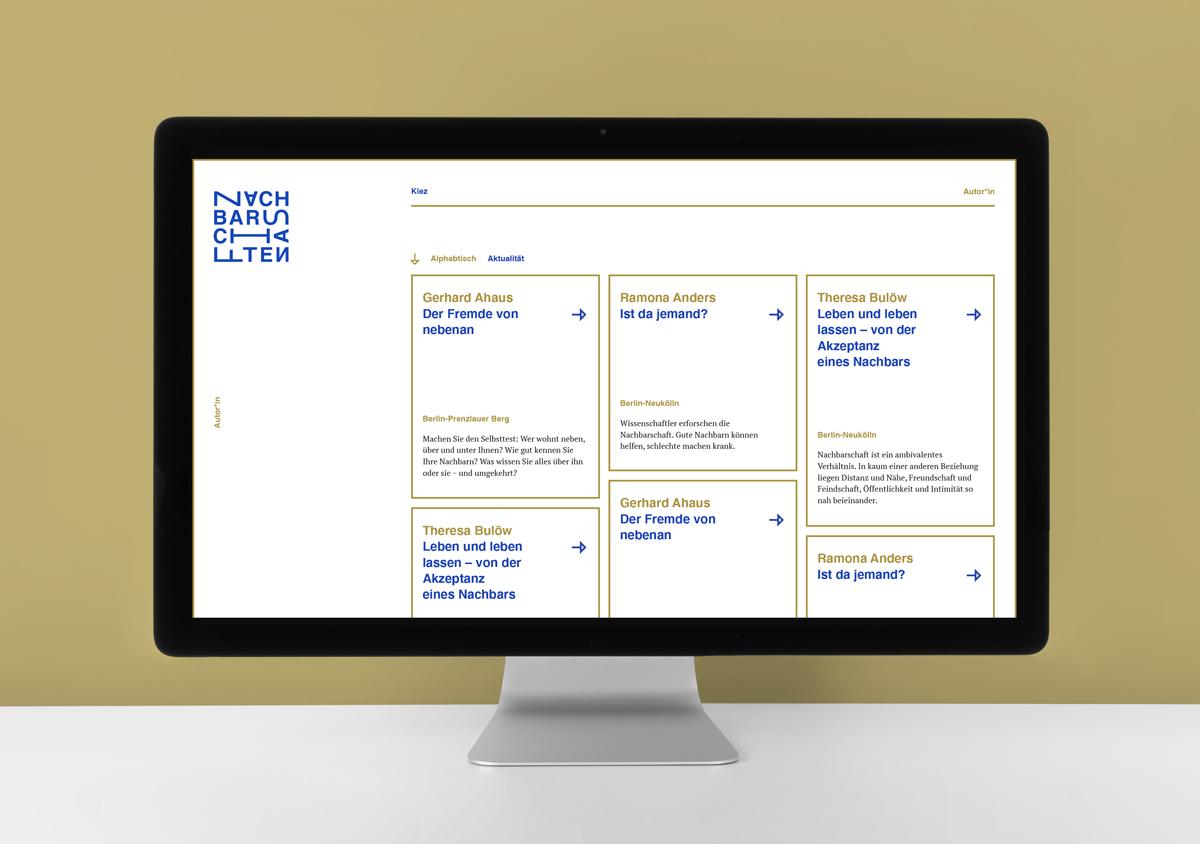 Desktop Bildschirm iMac auf grauer Tischplatte vor goldener Wand Auf dem Bildschirm Listenansicht der Kieze Website mit Kacheln blau goldener Text goldene lineare Umrandung
