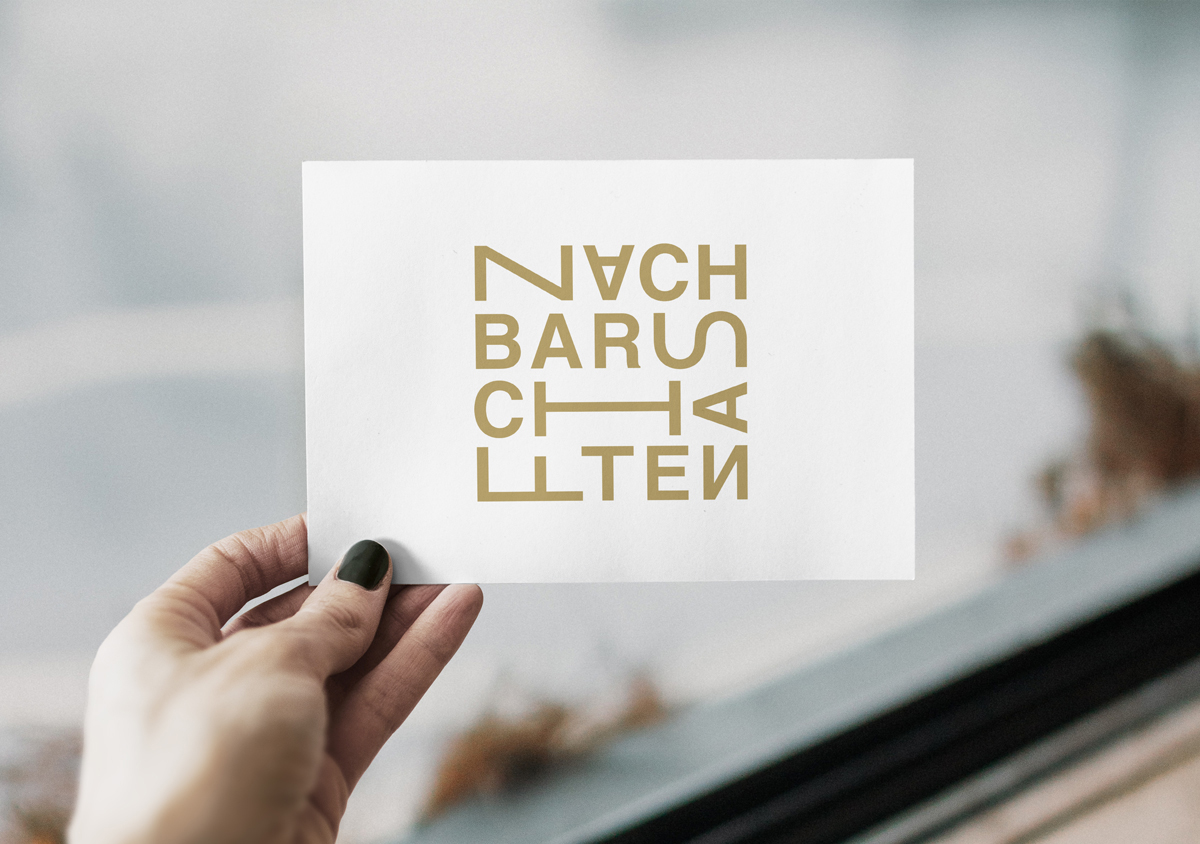 Hand mit lackierten Fingernägeln hält Karte hoch Logo in gold auf weißer Postkarte unscharfer Hintergrund