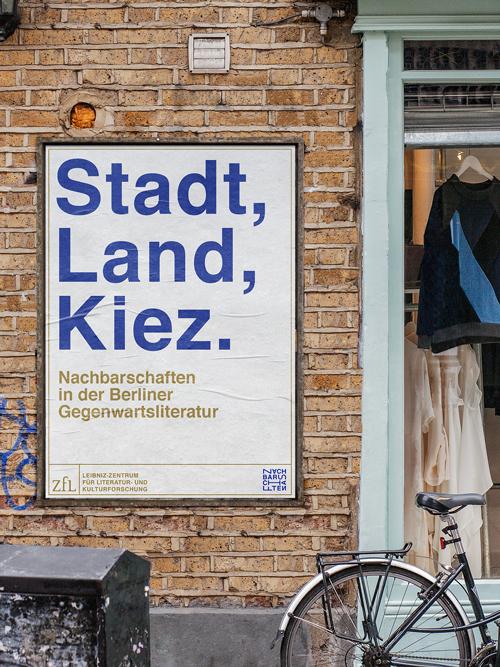 Plakat Außenwerbung an Backsteinmauer neben Eingang zu Bekleidungsgeschäft Layout: weißes DIN A1 Plakat mit großer blauer Headline