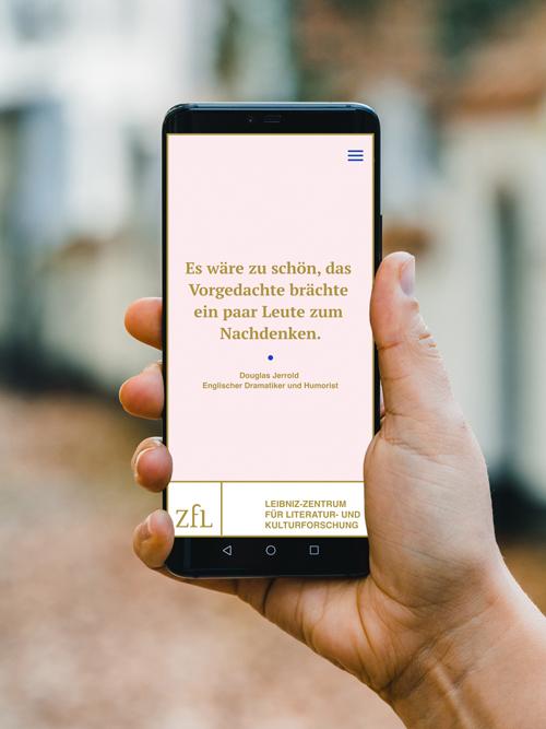Hand hält schwarzes Smartphone Zitatbereich der Website Zitat in gold auf rosa Hintergrund unscharfer Hintergrund hinter der Hand