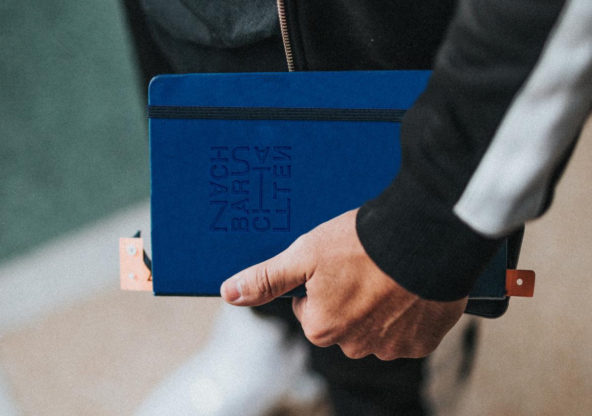 Blick von oben auf angeschnittene Person Ärmel einer schwarzen Sportjacke Hand hält blaues Notizbuch mit geprägtem Logo unscharf im Hintergrund weiße Turnschuhe