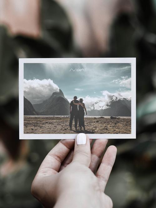 Mia, Myself and I Artwork Hand hält Postkarte Logo MMI Landschaftsbild Berge Wolken blauer Himmel Paar Arm in Arm