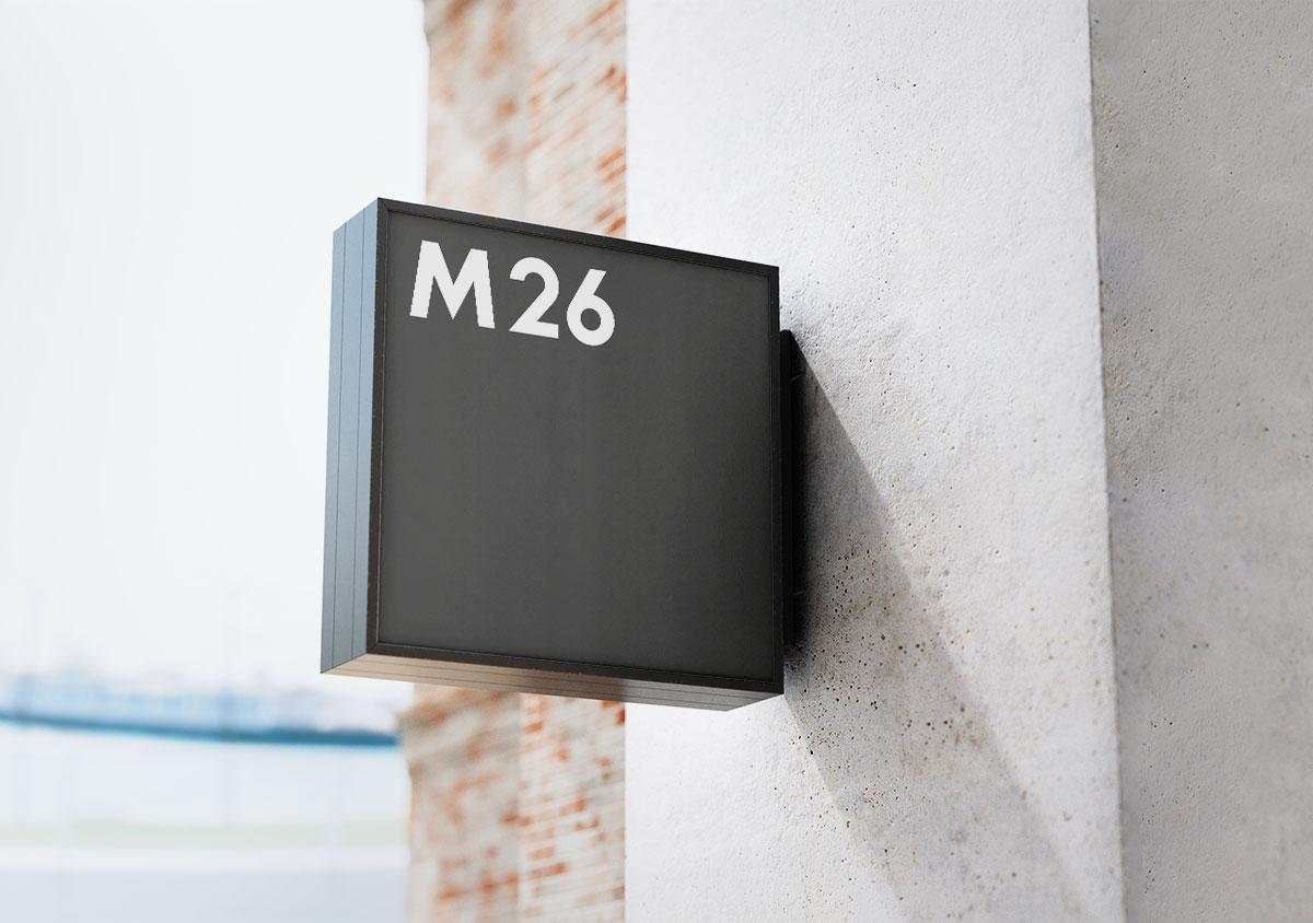 M26 Logo als schwarzes quadratisches Ladenschild an weisser Hauswand