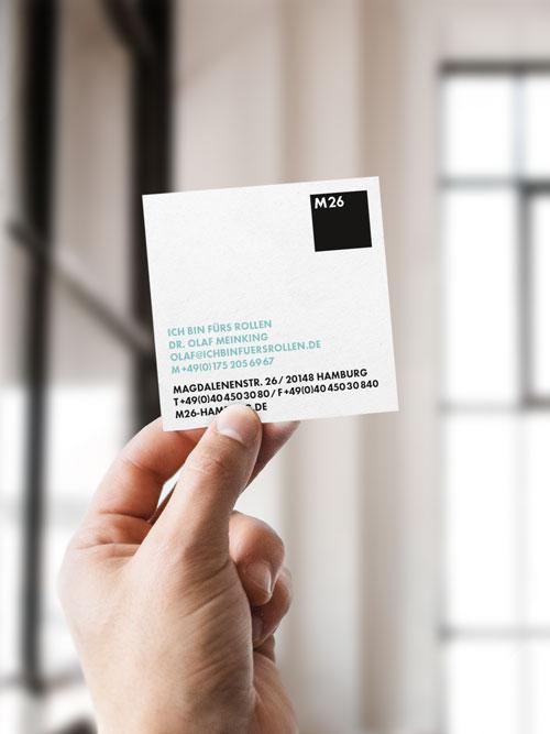M26 Visitenkarte weiss und quadratisch wird von Hand hoch gehalten Rückseite mit Logo und Text in schwarz und blau im Hintergrund heller Raum Loft