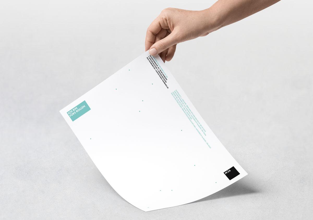 M26 Briefbogen weisses DIN A4 Blatt wird von Hand an einer Ecke hoch gehalten mit Logo und Text in schwarz und blau vor grauem Hintergrund