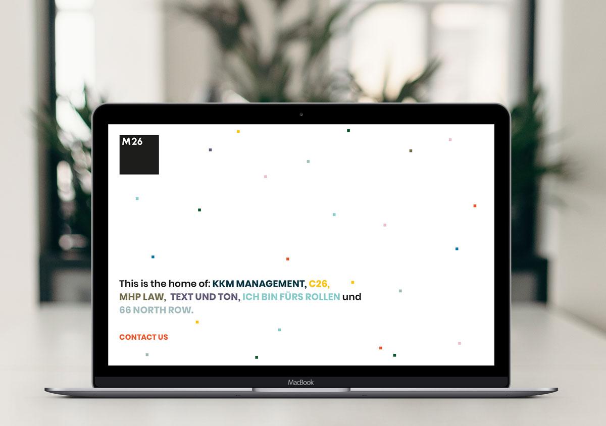Aufgeklappter Laptop auf Tisch im Hintergrund unscharfer Raum mit Pflanze auf dem Bildschirm M26 Coming-Soon Website weißer Logo und Text auf weißem Hintergrund mit buntem feinem Muster aus kleinen Quadraten
