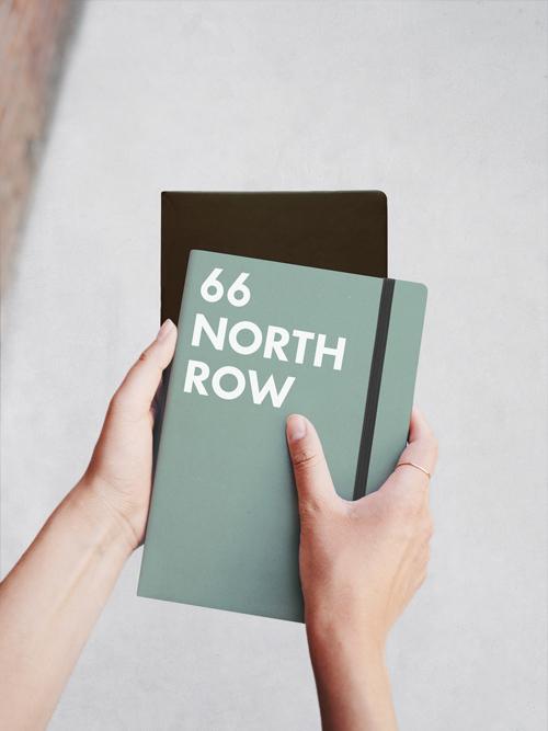 M26 Sketchbook Haende halten zwei Notizbuecher oben liegt ein gruen-graues mit schwarzem Gummiband darunter ist ein schwarzes Buch zu sehen auf dem ersten Sketchbook steht 66 NORTH ROW in weißen Buchstaben