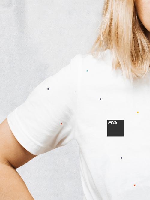 Blonde Frau im Anschnitt traegt ein weißes M26 T-Shirt mit kleinen farbigen Quadraten darauf Auf Brusthöhe sitzt das schwarze M26 Logo