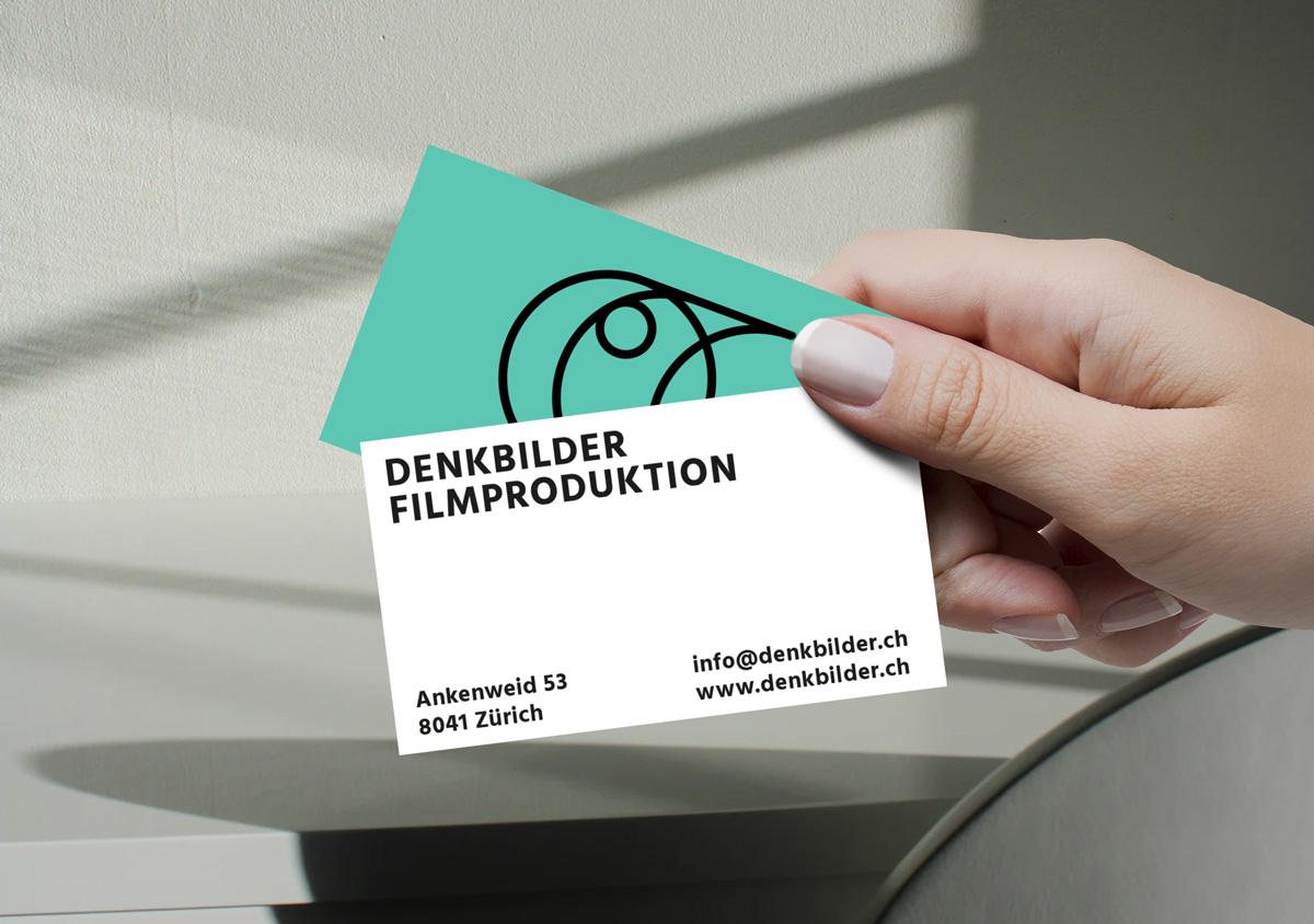 Denkbilder Filmproduktion Hand hält zwei Visitenkarten Vorderseite schwarzes Bildzeichen auf grüner Fläche Rückseite Adresse schwarzer Text auf weiß