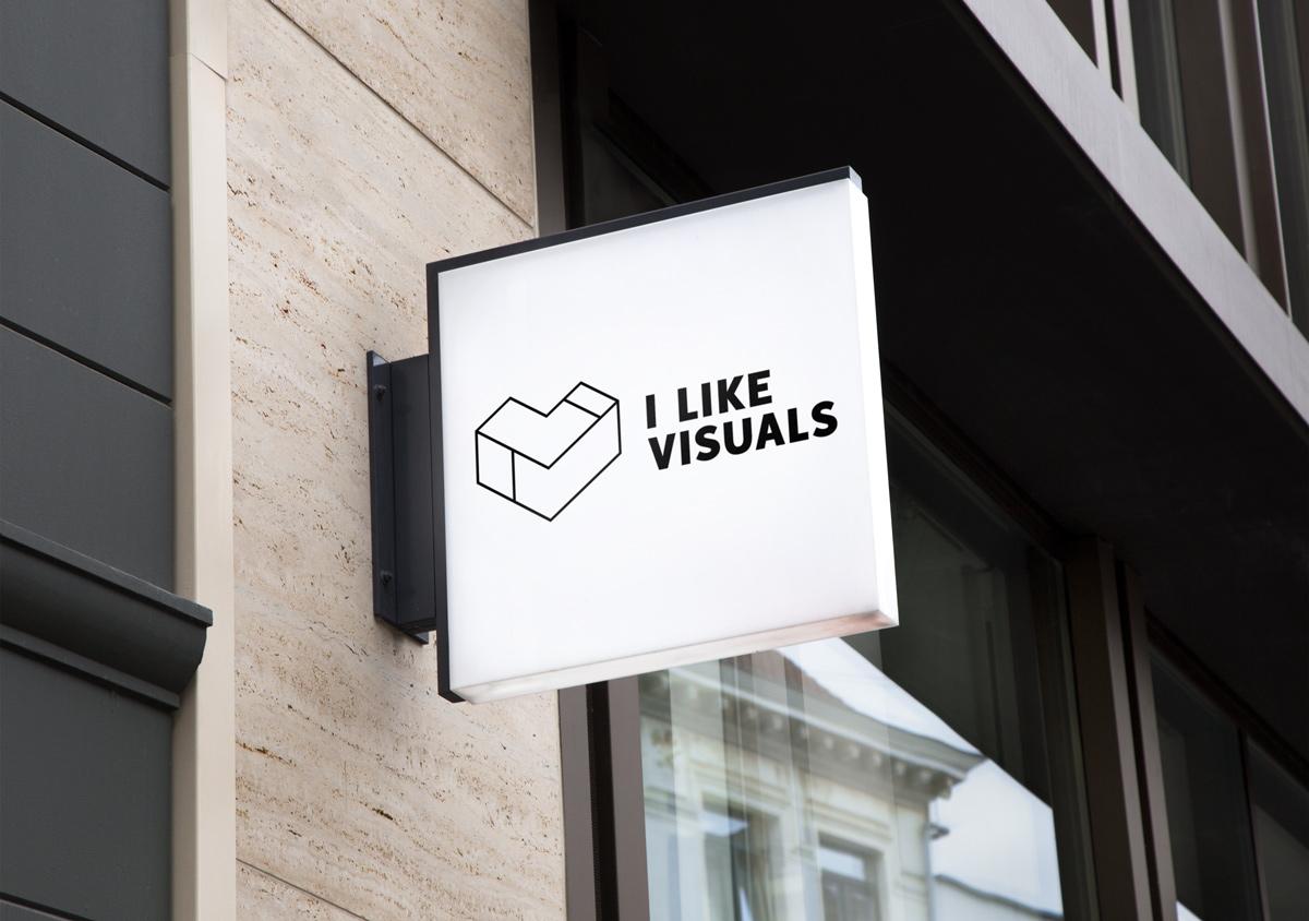 Logo in linear schwarz von I Like Visuals an Hausfassade auf weißem Ladenschild
