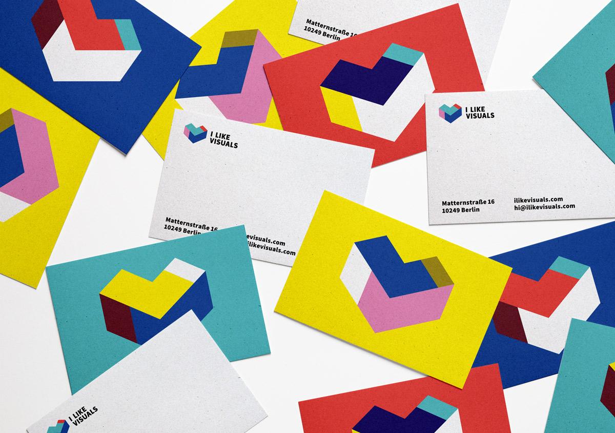 Visitenkarten ungeordneter Stapel auf weißem Untergrund Vorderseite mit verschieden farbigen Logos weiße Rückseite mit I Like Visuals-Logo und Adresse
