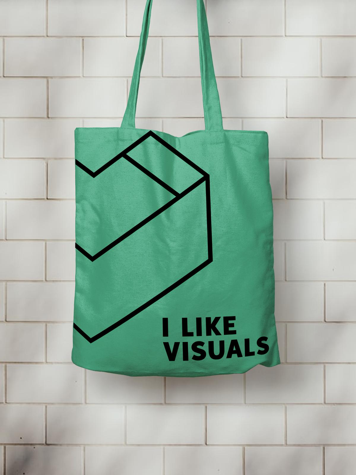 I Like Visuals grüner Beutel mit schwarzem linearen Logo Druck vor weißer Backsteinwand