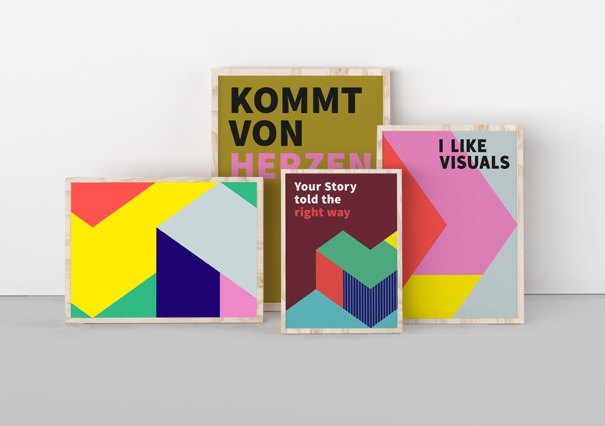 Vier Bilderrahmen aus hellem Holz mit I Like Visuals Postern stehen vor einer Wand gestapelt in einem hellen Raum Text, Logo- und Grafikelemente sind auf den Plakaten zu sehen
