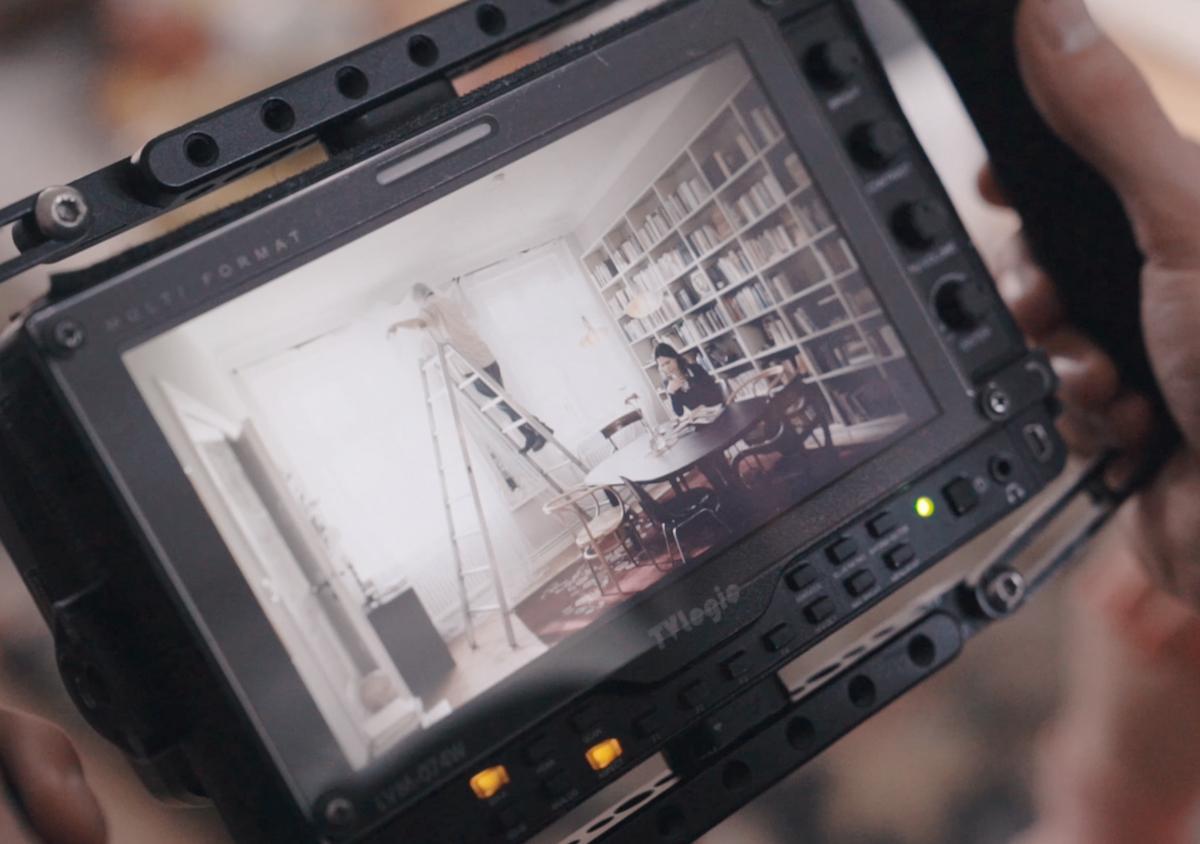 Behind the Scene I Like Visuals Blick über die Schulter auf den Kamerabildschirm Close up einer Kamera Motiv zwei Personen in einem Wohnzimmer Eine Frau sitzt auf dem Sofa Ein Mann steht auf einer großen Leiter und hängt Gardinen auf