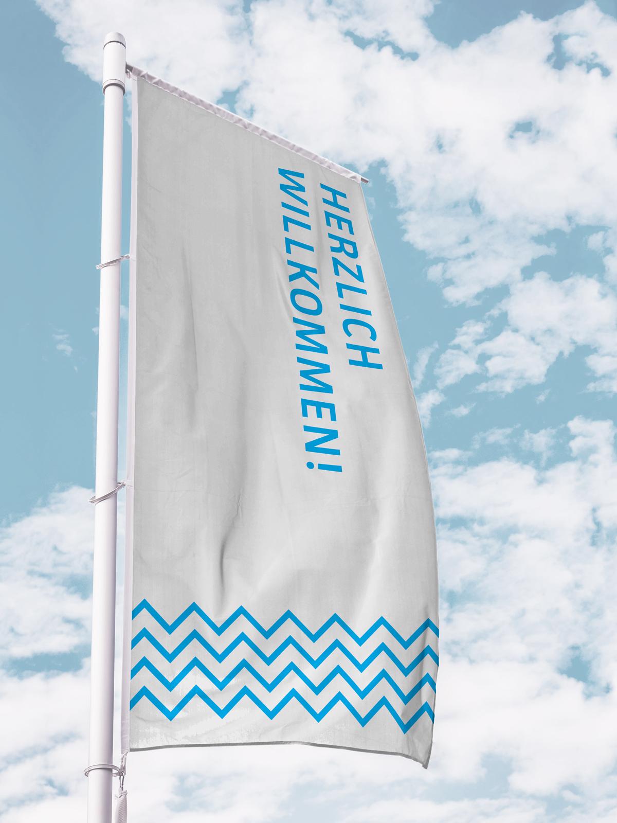Küstenmuseum Wilhelmshaven Sonderausstellung 150 Jahre Wilhelmshaven wehende weiße Fahne mit blauer Schrift vor blauem Himmel Text Herzlich Willkommen! gekippt am rechten Flaggenrand Unten Bordüre mit blauen Zickzacklinien
