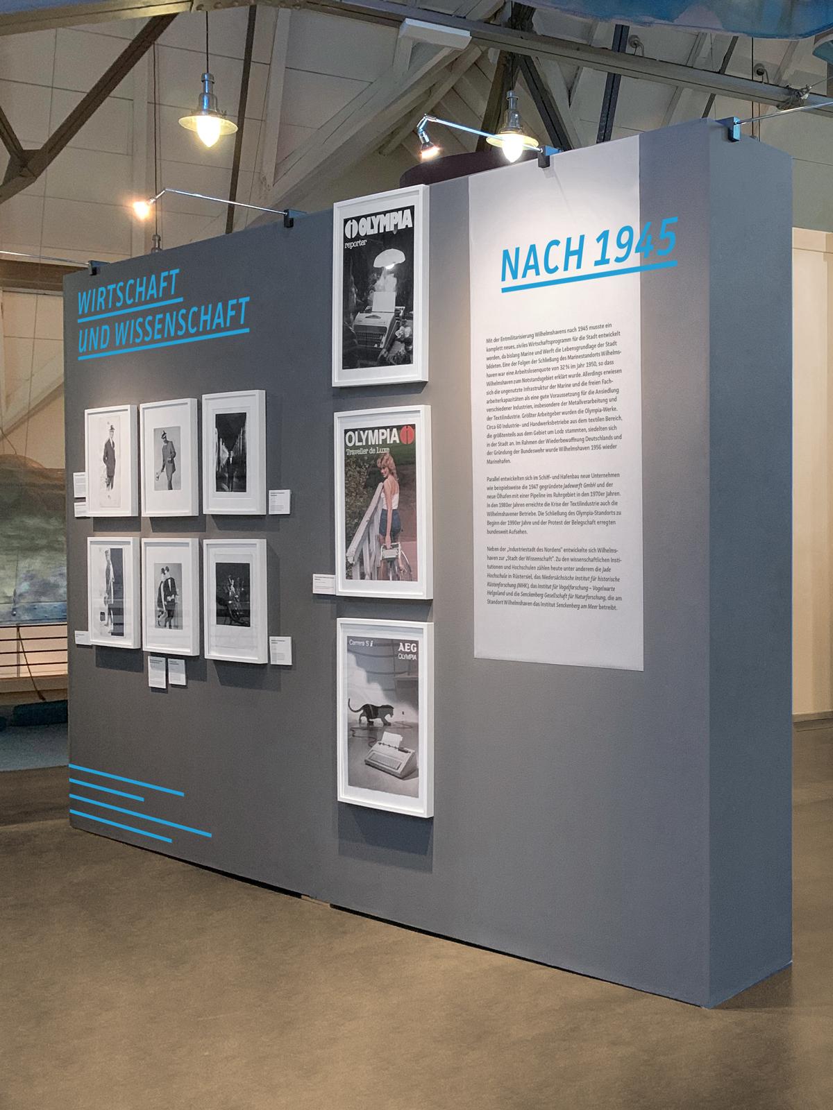 Küstenmuseum Wilhelmshaven Sonderausstellung 150 Jahre Wilhelmshaven Fotografie von Ausstellungswand dunkelgrauer Hintergrund blaue und schwarze Typografie grafische Zickzacklinie in blau am unteren Rand weiße Bilderrahmen