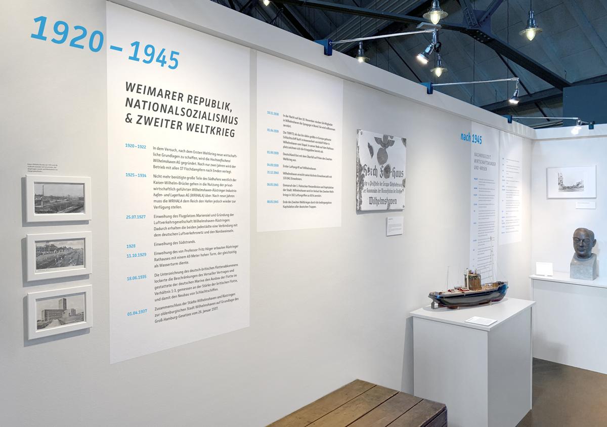 Küstenmuseum Wilhelmshaven Sonderausstellung 150 Jahre Wilhelmshaven Fotografie von Ausstellungswand hellgrauer Hintergrund blaue und schwarze Typografie grafische Zickzacklinie in blau am unteren Rand weiße Bilderrahmen Ausstellungsobjekte auf Sockel ein Boot und eine Kiste Emailleschild an der Wand
